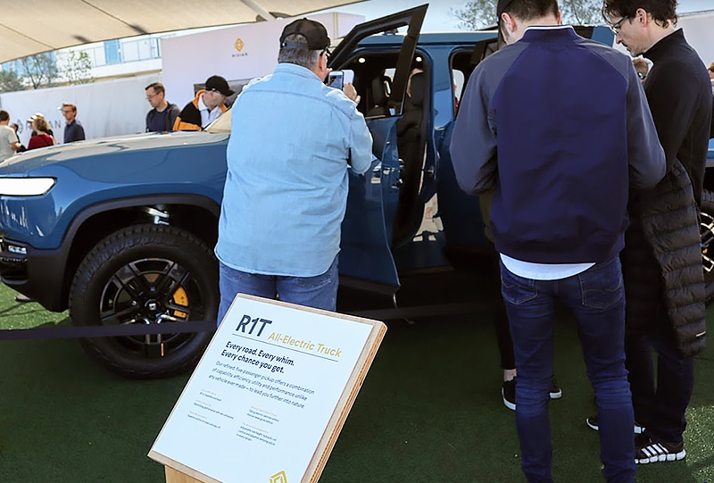 Interested attendees at Fully Charged LIVE USA peer into a Rivian R1T on display